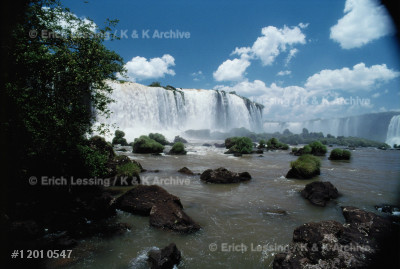 """Iguacu Falls,shared by Argentina and Brazil,resemble   an elongated horseshoe that extends for almost 3 kms,  nearly three times wider than the Niagara Falls. In    some 275 separate waterfalls,the Iguacu river plunges  down 80 meters into the """"Devil's Gorge""""."""