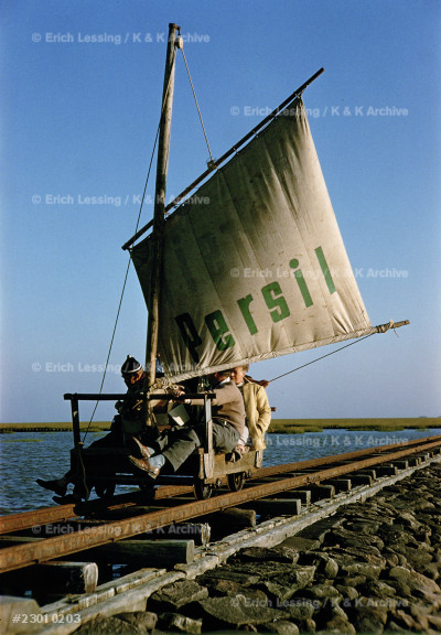 Platform with sail on rails, connecting the Halligen islands in the North Sea, Germany. The sail is advertising Persil washing powder. During low tide, the islands can be reached on foot. 1958.