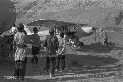 In 1952 locust swarms flying in from Saudi Arabia threatened Iran's harvest. In a unique cooperation, US and Soviet pilots and specialists sprayed the infested areas.  US-pilot Jim Springer cranks his Piper-cub, local boys watch.