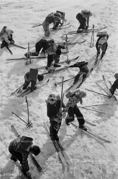 Children in the Austrian Enns valley scrambling to get their skis off after skiing to school, 1953.