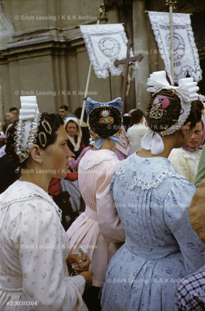 Women with  beribboned caps and paste-studded combs walk in the Corpus Christi procession in Kalocsa, on May 31, 1956.