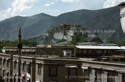 The Red Mountain, holy mountain of the Tibetan         Buddhists, with the Red and White Palace of Potala,    seen above modern buildings in Lhasa.