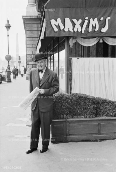 """Chansonnier Maurice Chevalier interprets his song:      """"Un gentleman, en hiver comme en ete, porte toujours un chapeau Locke bien bombe, et par un temps de pluie il n'ouvre jamais, jamais, son parapluie."""" Paris, 1954"""