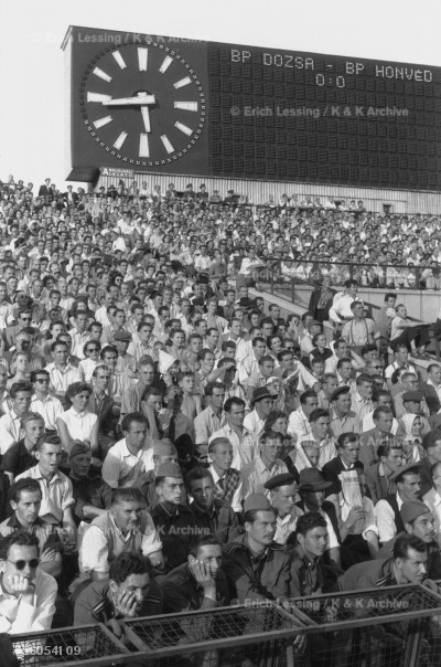 A soccer game in Budapest, 1956. This was the time of  Ferenc Puskas, the major who played for the Kispest-Honved army team, the man who only used his left foot, could not head and nevertheless shot 83 international goals during his career at Honved, and, after the Hungarian Revolution, for Real Madrid.