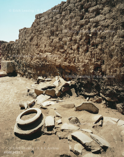 Crumbling brick walls and large broken storage jars.   