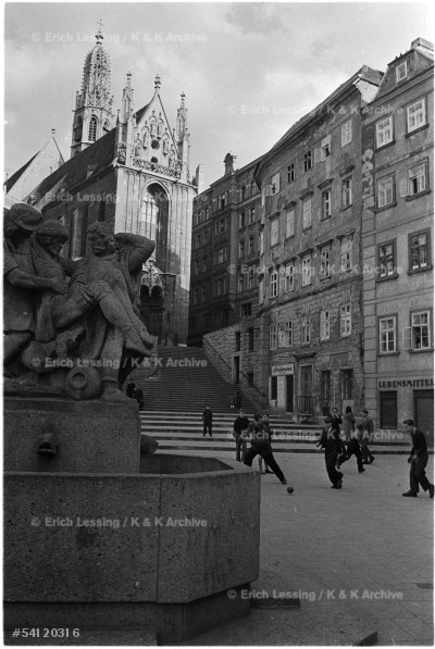 Children playing soccer in front of the Maria am Gestade chruch. Life in post-war Vienna.